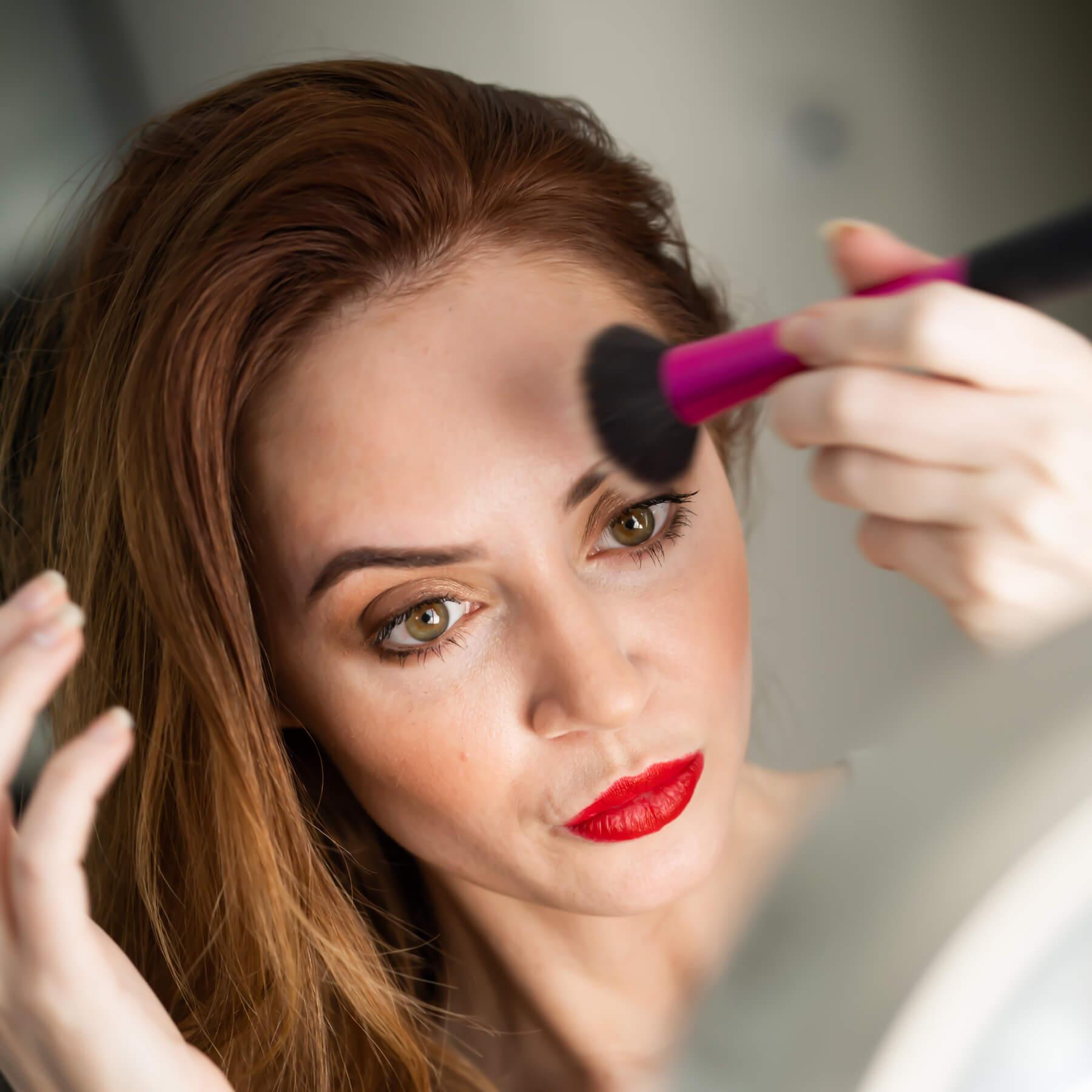 Woman applying make-up with powder brush
