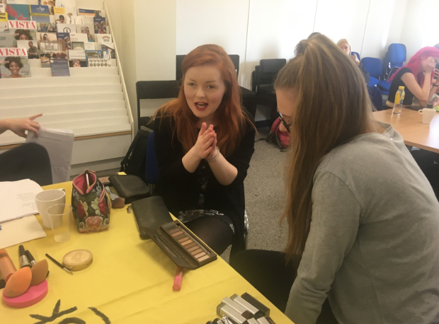Lucy Edward as she gives a beauty consultation to one of the workshop participants. Lucy is pictured at a table, with lots of different types of make-up laid out before her