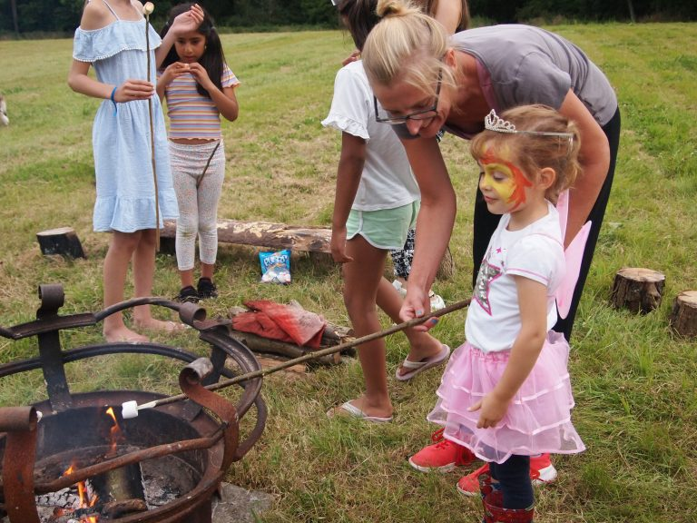 view of young girl with lady helping her toast marshmallow over fire pit with other children in background