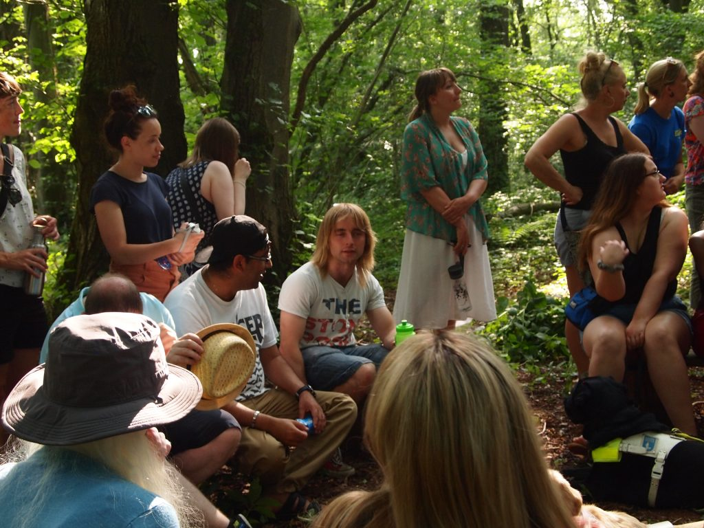 large group of volunteers sat at the fire pit in the forest.