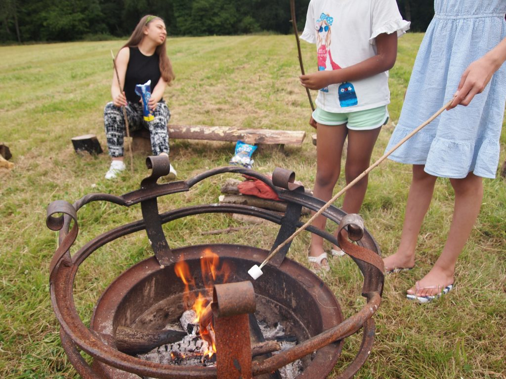 children toasting marshmallows at the fire pit.