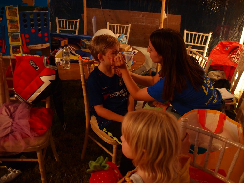 a volunteer face painting a young boy