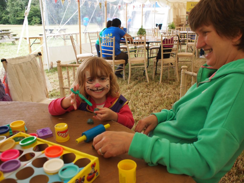 child playing with play dough with a pained face beaming at the camera, her mother is sat beside her.