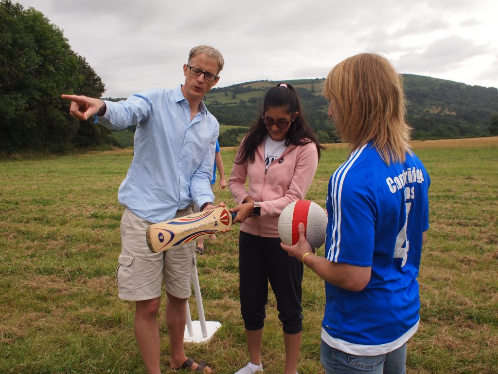 a parent, and volunteer warren show Maleeka how to play blind cricket.
