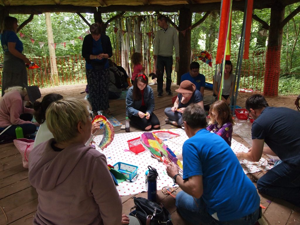 volunteers, parents, and children making festival decorations in the wooden roundhouse.