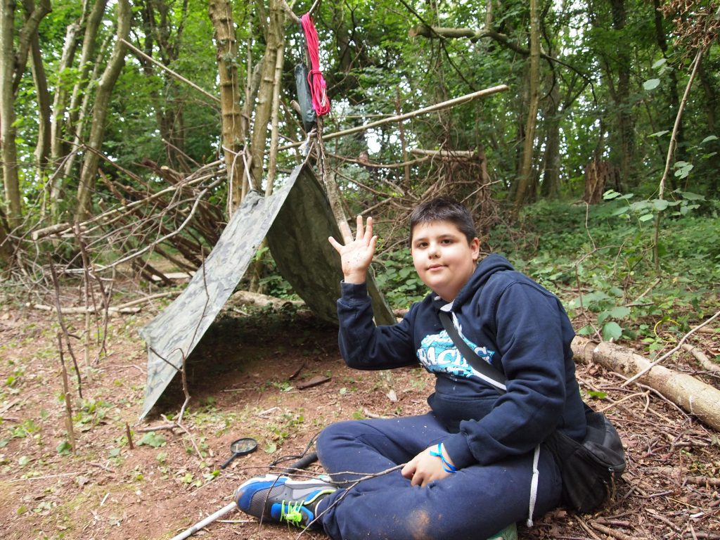 a kid poses proudly next to his den.