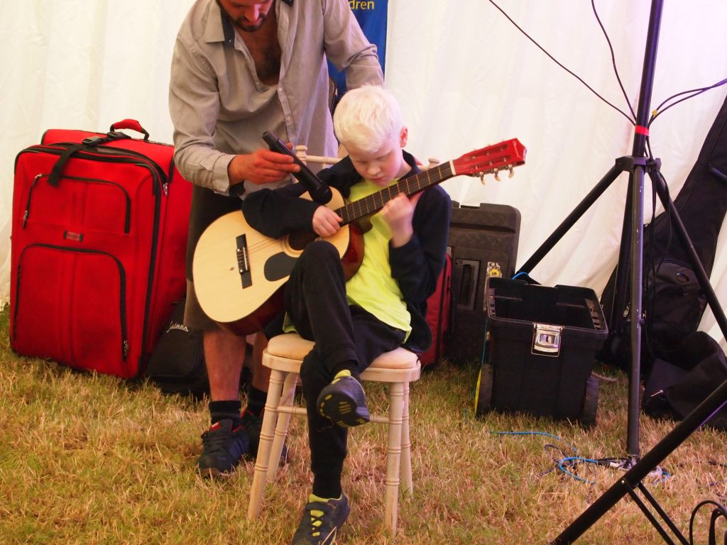 a young boy playing his guitar, tech person holds a microphone for him.