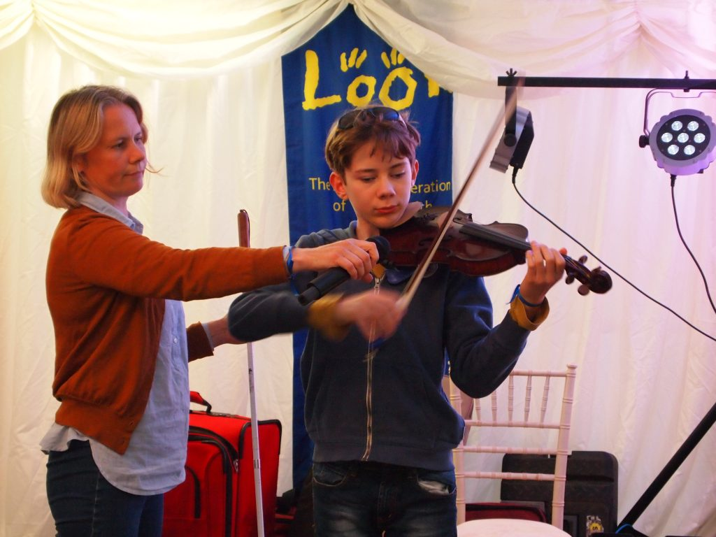 theo playing his violin, his mother is holding up a microphone beside him.