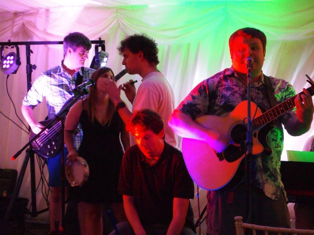 Unchained Melody,  band on stage, a view of five people playing, guitar, cajon, tambourine, and bass.