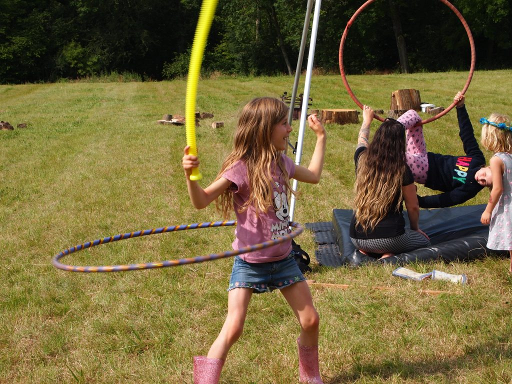 children in circus workshop, young girl in the foreground is hulahooping.