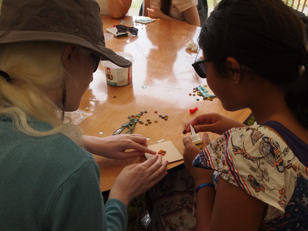 a mentor helping a young girl make a mosaic