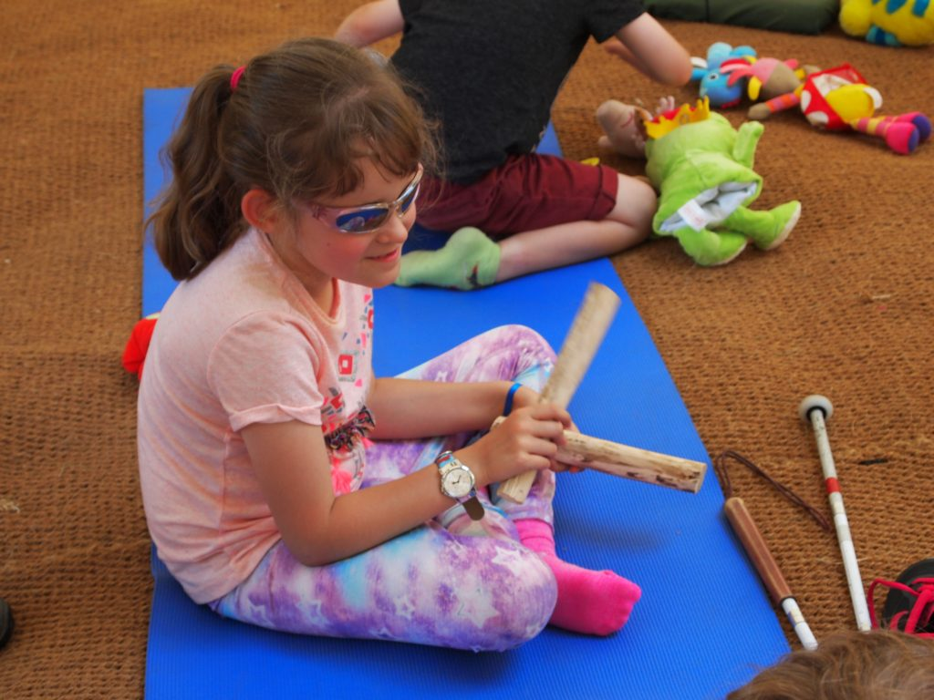 young girl playing with her percussive wooden sticks.