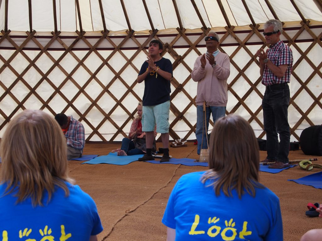 view of InnerVIsion facilitators in the yurt and the backs of two volunteers in the foreground.