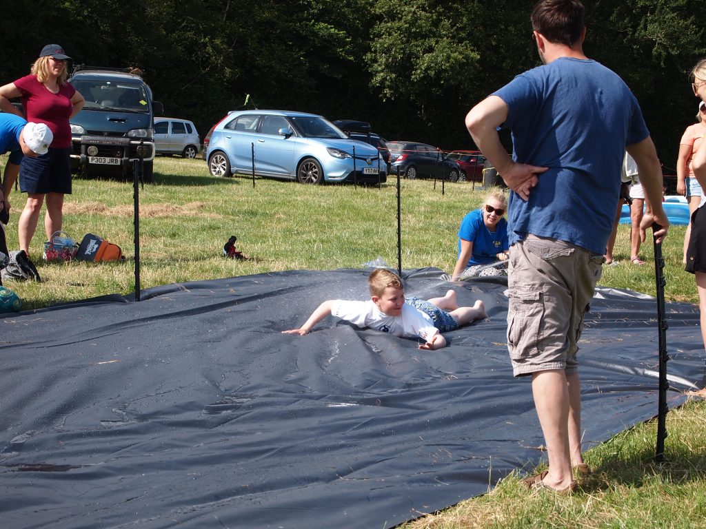 parents stood around a slip and slide, a young boy is sliding down on his stomach.
