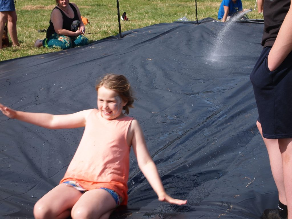 young girl sliding down slip and slide on her knees.