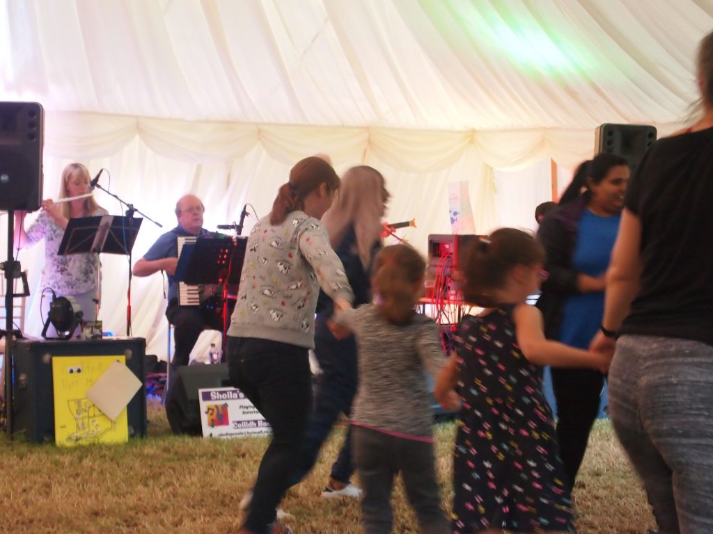 children and young people dancing before a ceilidh band. a lady on flute, a man playing the accordion and a man on fiddle.