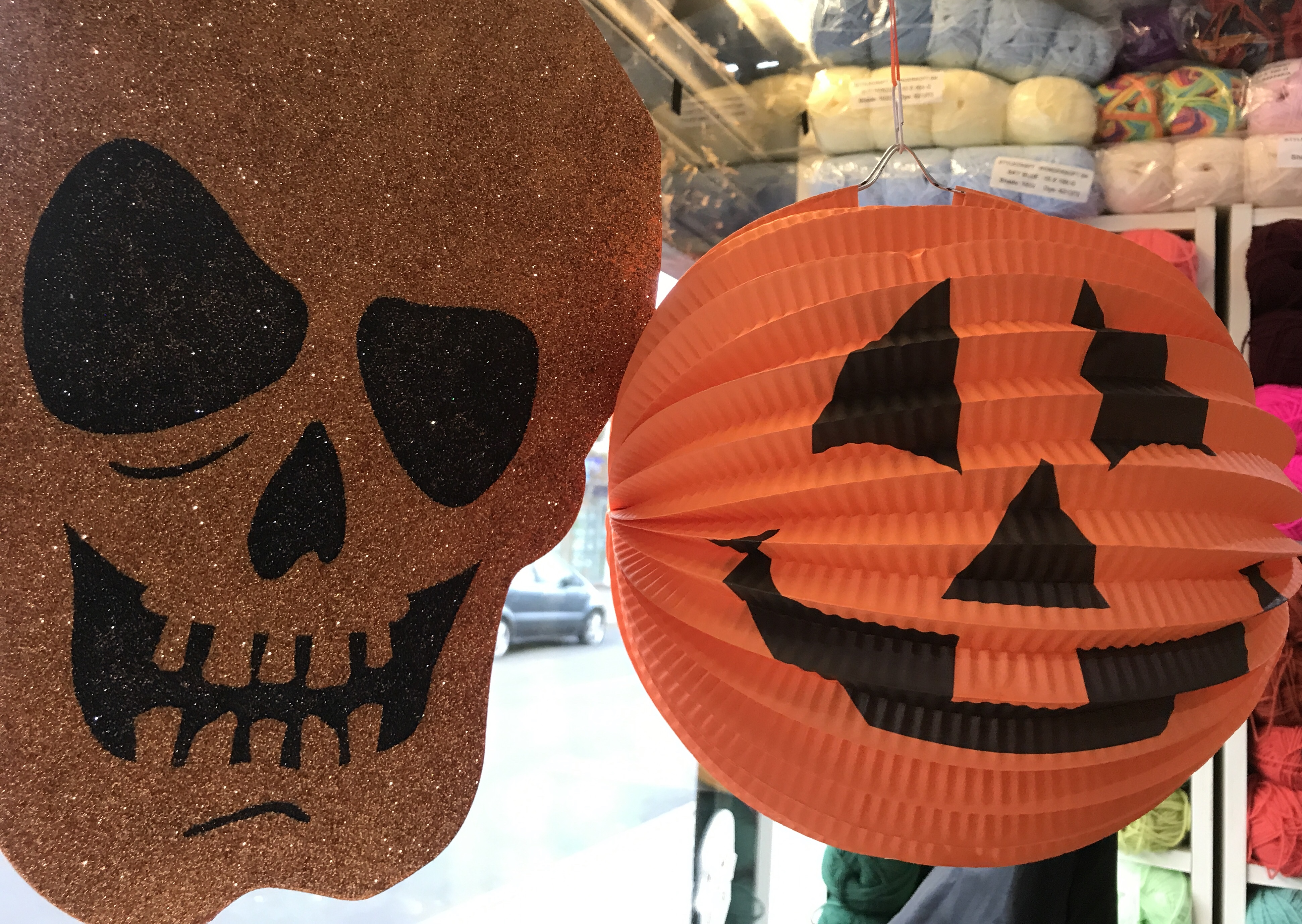picture of halloween decorations, a glittery skull and a pumpkin lantern.