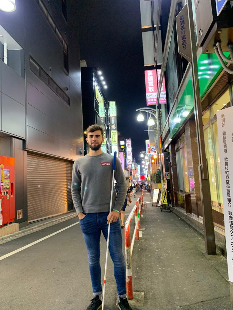 picture of chris standing with his cane at night on a street in Japan.