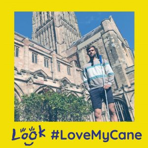 image of chris posing outside a cathedral with his cane. image is framed with yellow love my cane branding.