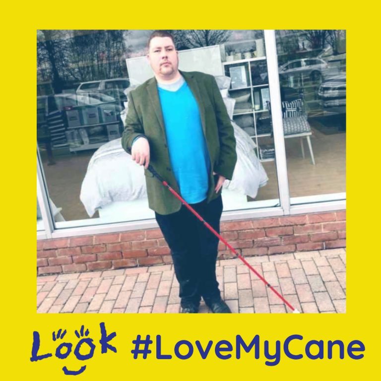 Luke stood on some grey stone paving in front of a large rectangular window wearing a medium green jacket, a bright blue jumper, a pair of black trousers, and a pair of black Leather boots holding a long red cane, on a light background. image is framed with love my cane hashtag campaign logo and the look logo.
