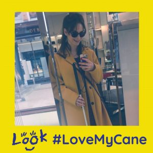 mirror selfie of chloe holding cane, and wearing sunglasses. image is framed with yellow love my cane logo.