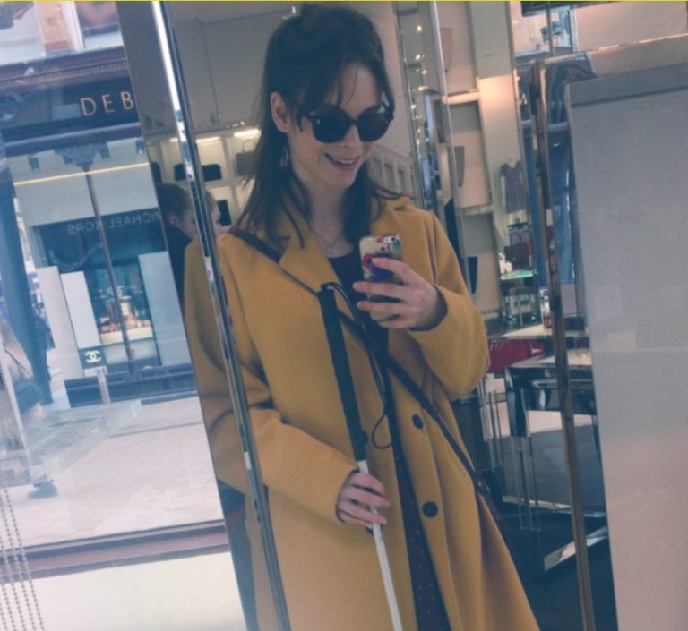 mirror selfie of chloe smiling in sunglasses in a department store, wearing a yellow long coat.