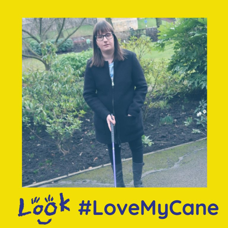 Holly Tuke standing with her purple cane on a park path. image is framed with the hashtag love my cane logo.