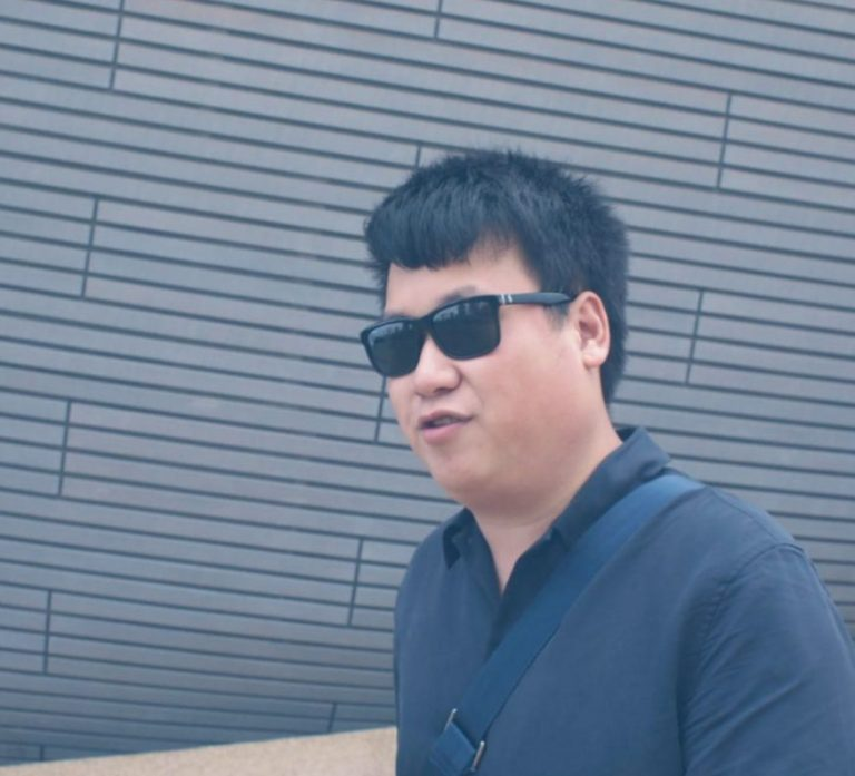 picture of alex, wearing sunglasses, smiling, infront o a modern looking building.