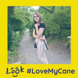 image of Elin smiling and holding cane, image is framed with yellow love my cane logo and look logo.
