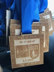 wooden medals that read 5k in aid of look and guide dogs, 4.1.2020. the writing is framed by the equivalent in braille.