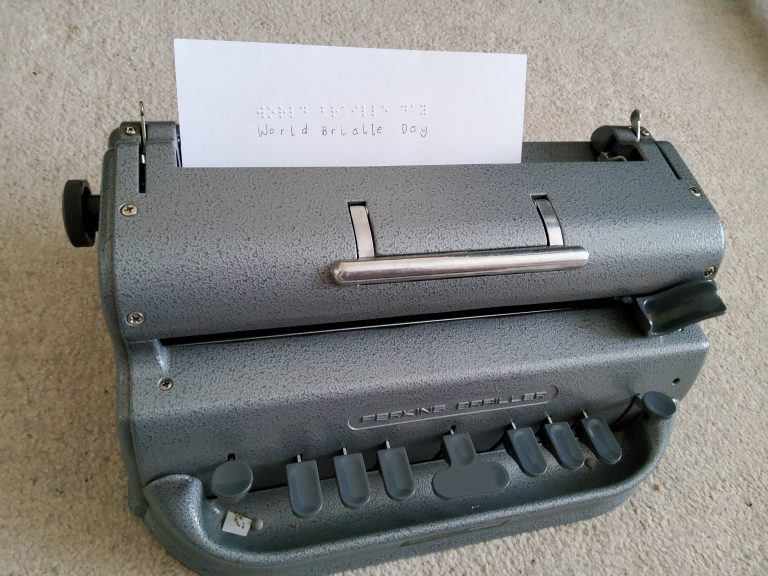 picture of braille machine, with words 'world braille day' typed and written on the piece of paper in the feed.
