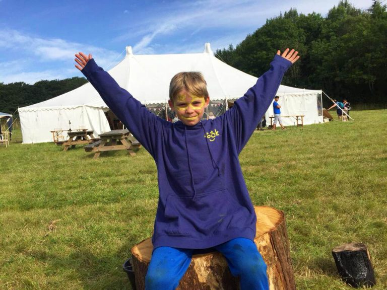 Boy with arms outstretch in front of marquee tent