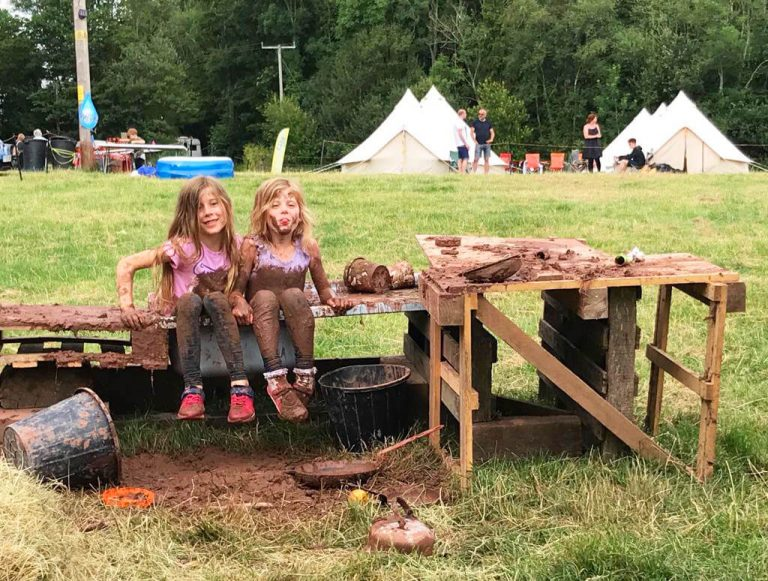 two girls playing in the mud kitchen