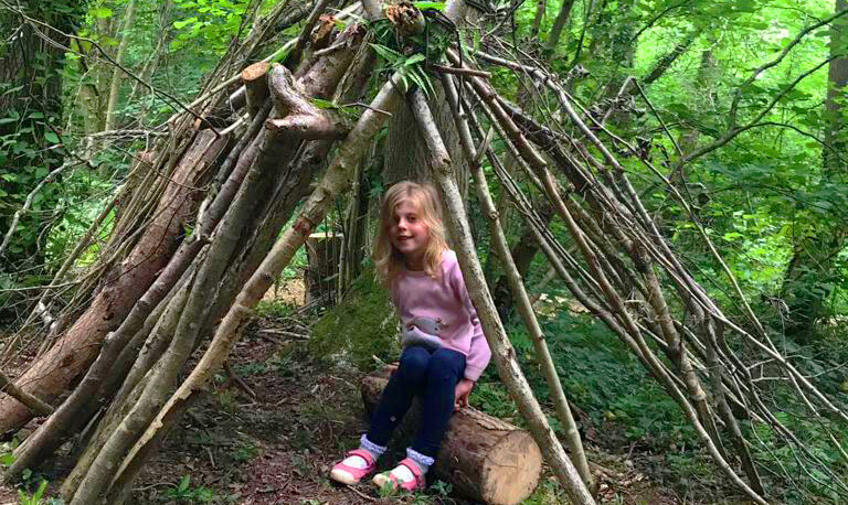 young girl playing in a den she made herself
