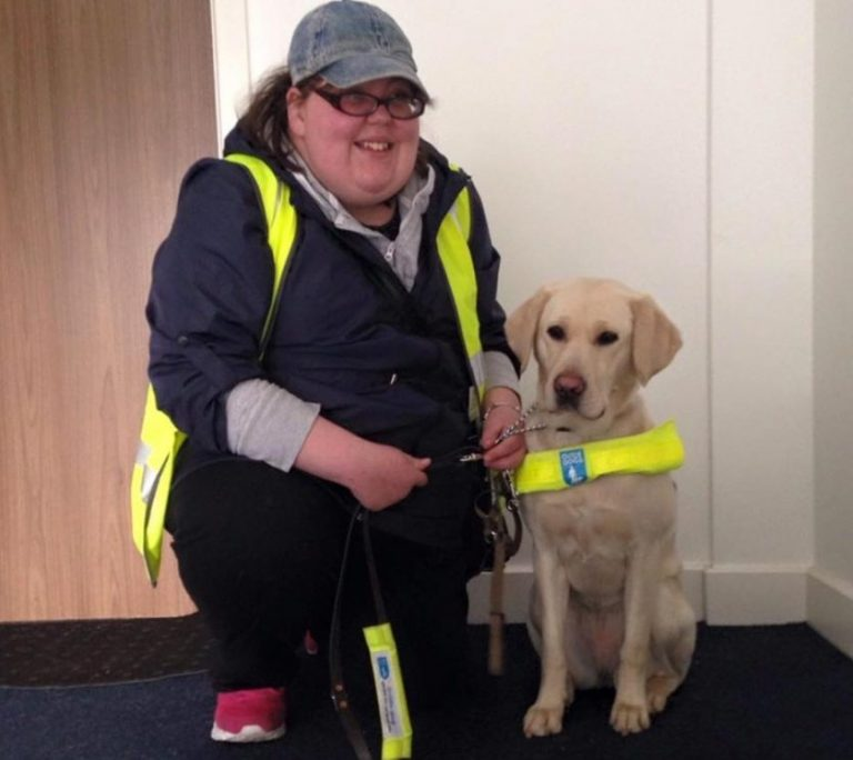 Michelle, wearing a cap and yellow high vis jacket, kneels down next to her golden labrador guide dog and smiles at the camera.