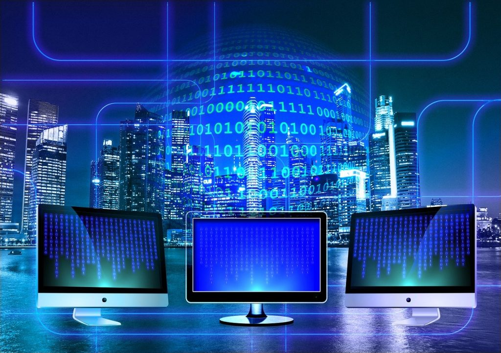 Three computer monitors with blue and black screens ad code on the,. A night-time cityscape of skyscrapers in the background. Binary written across the background.