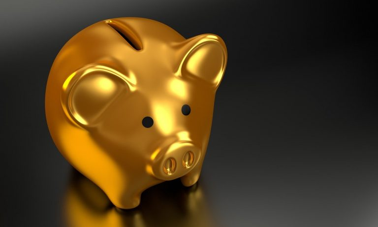 Gold piggy bank on a black table
