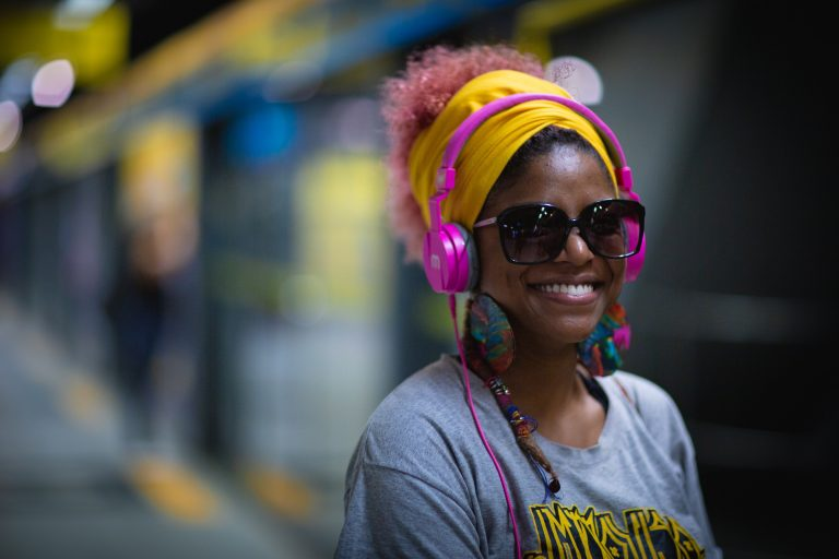 Woman wearing headphones and tinted glasses at train station, smiling.