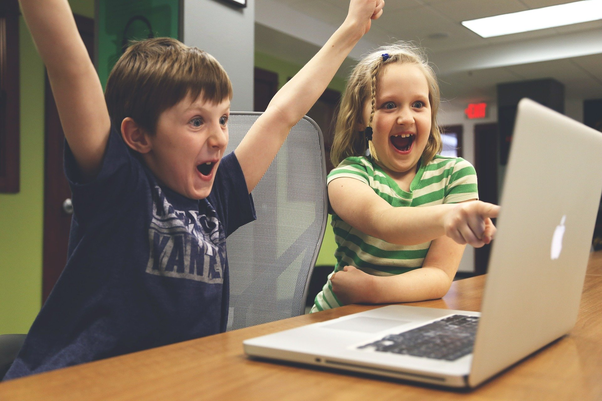 Image shows two young children looking and pointing at a laptop screen. The boy has his arms in the air, celebrating and the girl smiles broadly as sh e points at the screen