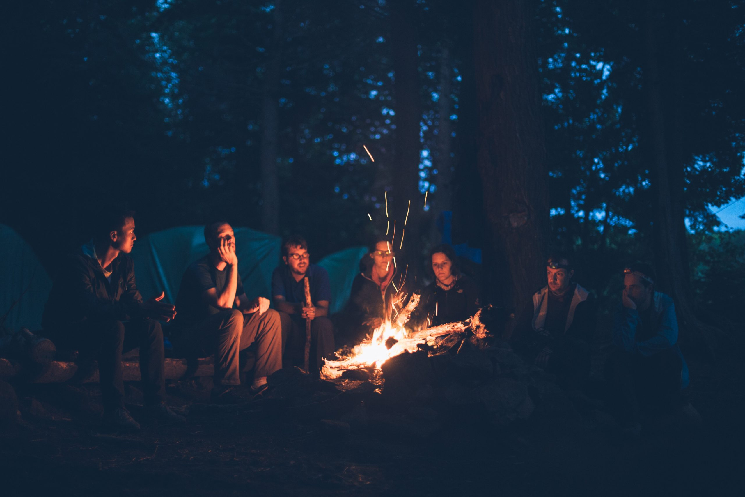 Omage shows young peole sat around a camp fire with a night sky backdrop.
