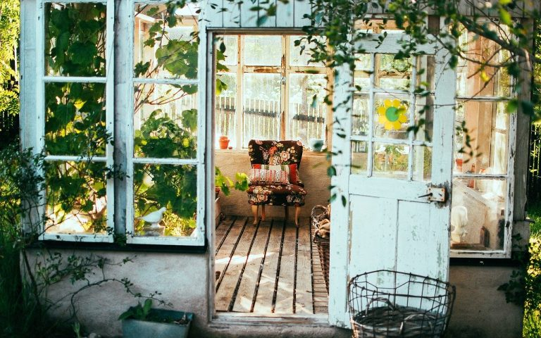 Image shows a patchwork armchair in a pretty summer house with flowers trailing the door.