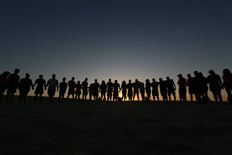 Silhouette of a group of teenagers stood in a line with the sunrise behind them.