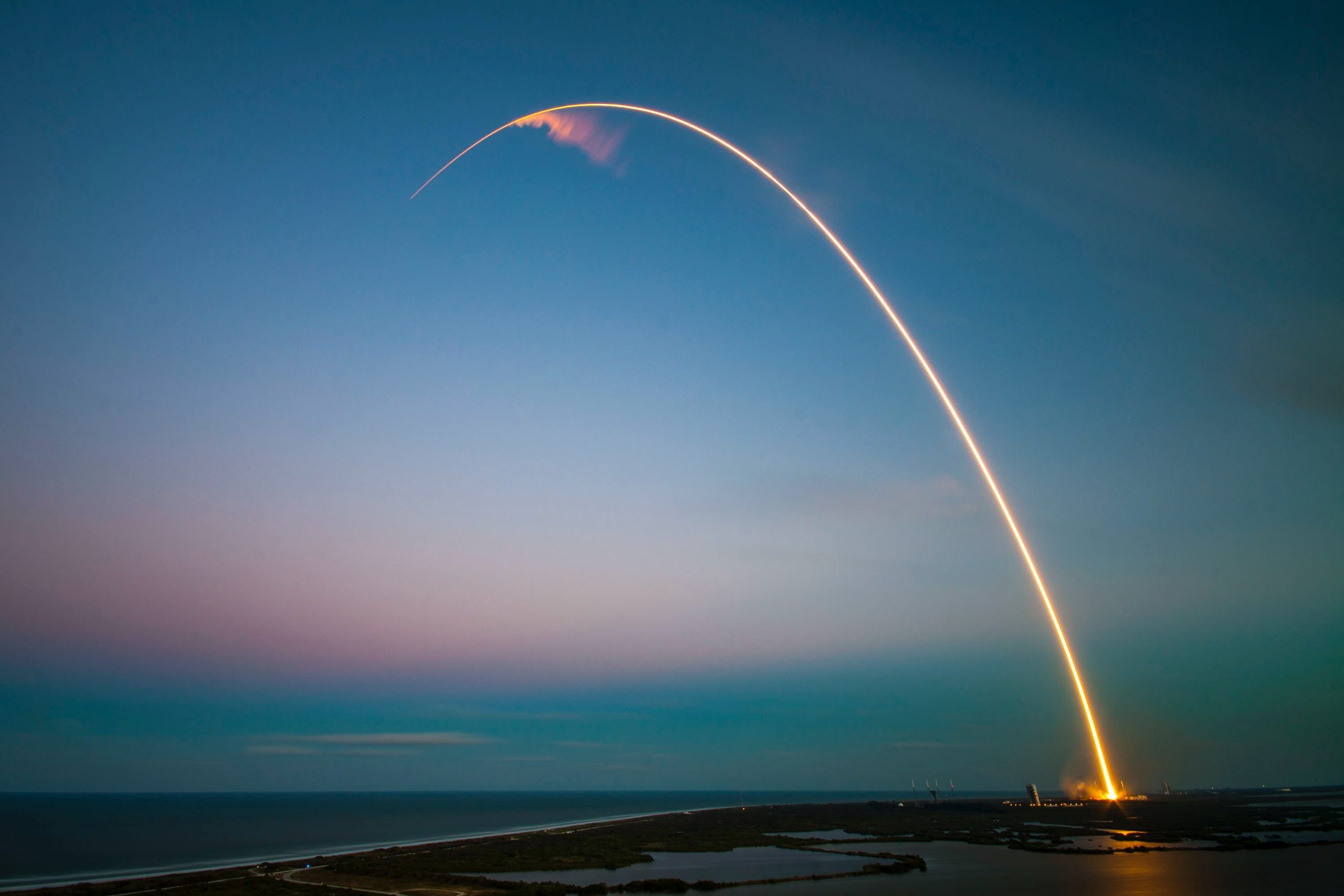Image shows the light trail of a rocket launching in an arc across a blue sky.