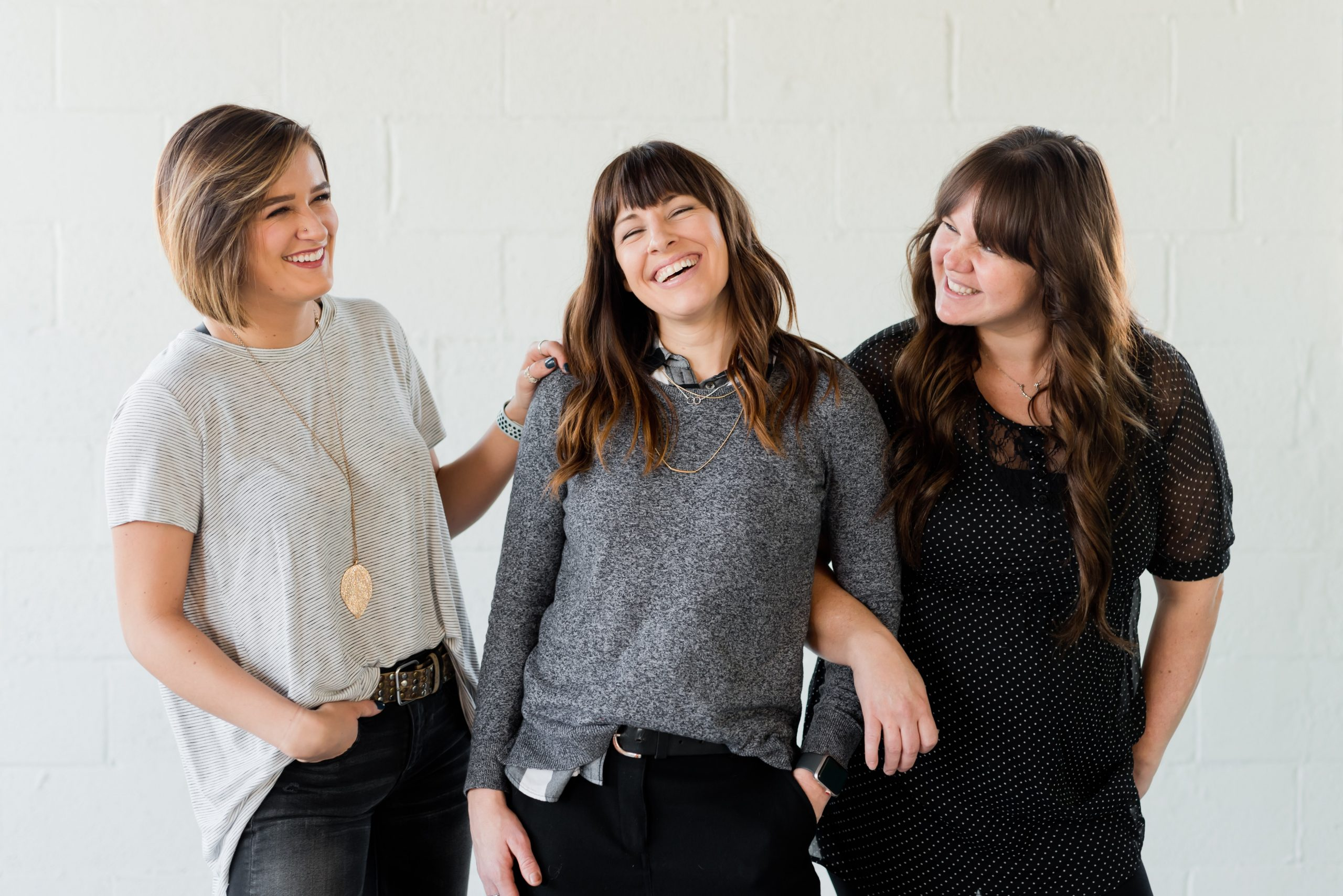 Image shows 3 girls stood arm in arm, smiling and sharing a laugh.