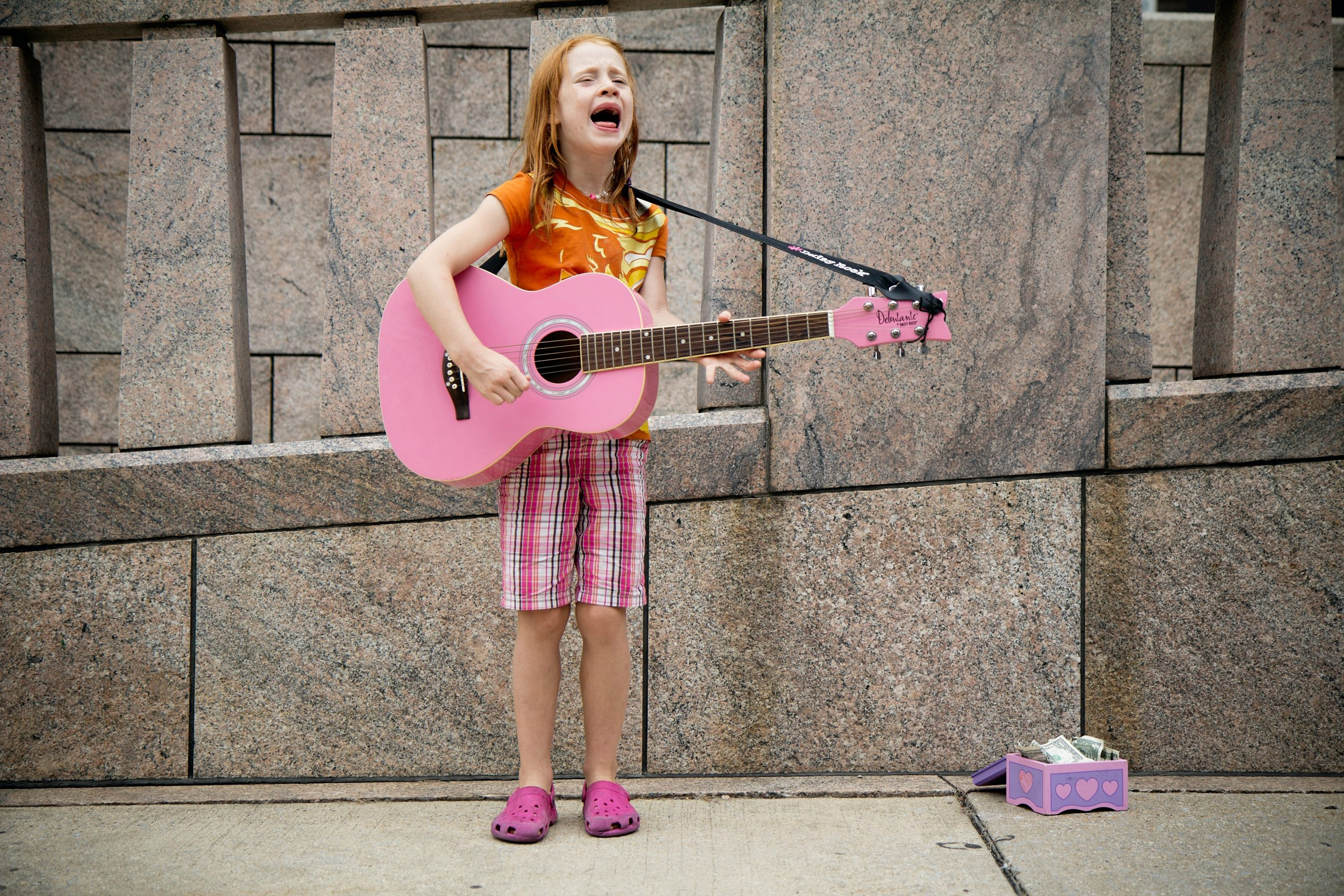 Young girl with red hair wearing pink checked shorts and an orange t-short, playing a pink guitar on a pavement, with a box of money on the floor.