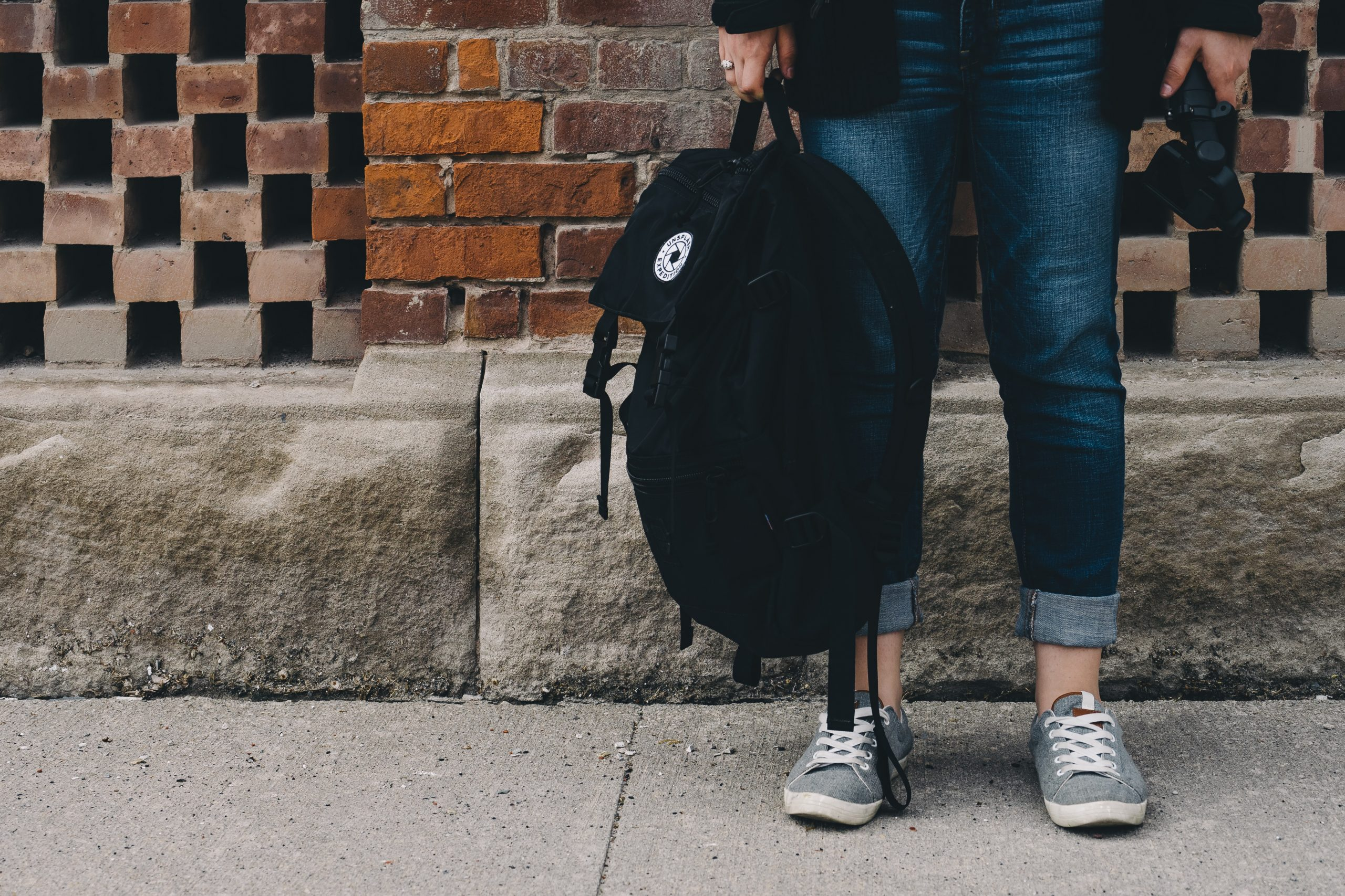 Image shows legs of a person standing near brick wall, holding black rucksack.