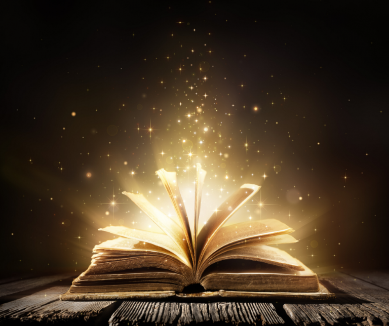 Image shows a book lay open with magical-looking gold dust emanating from its pages.