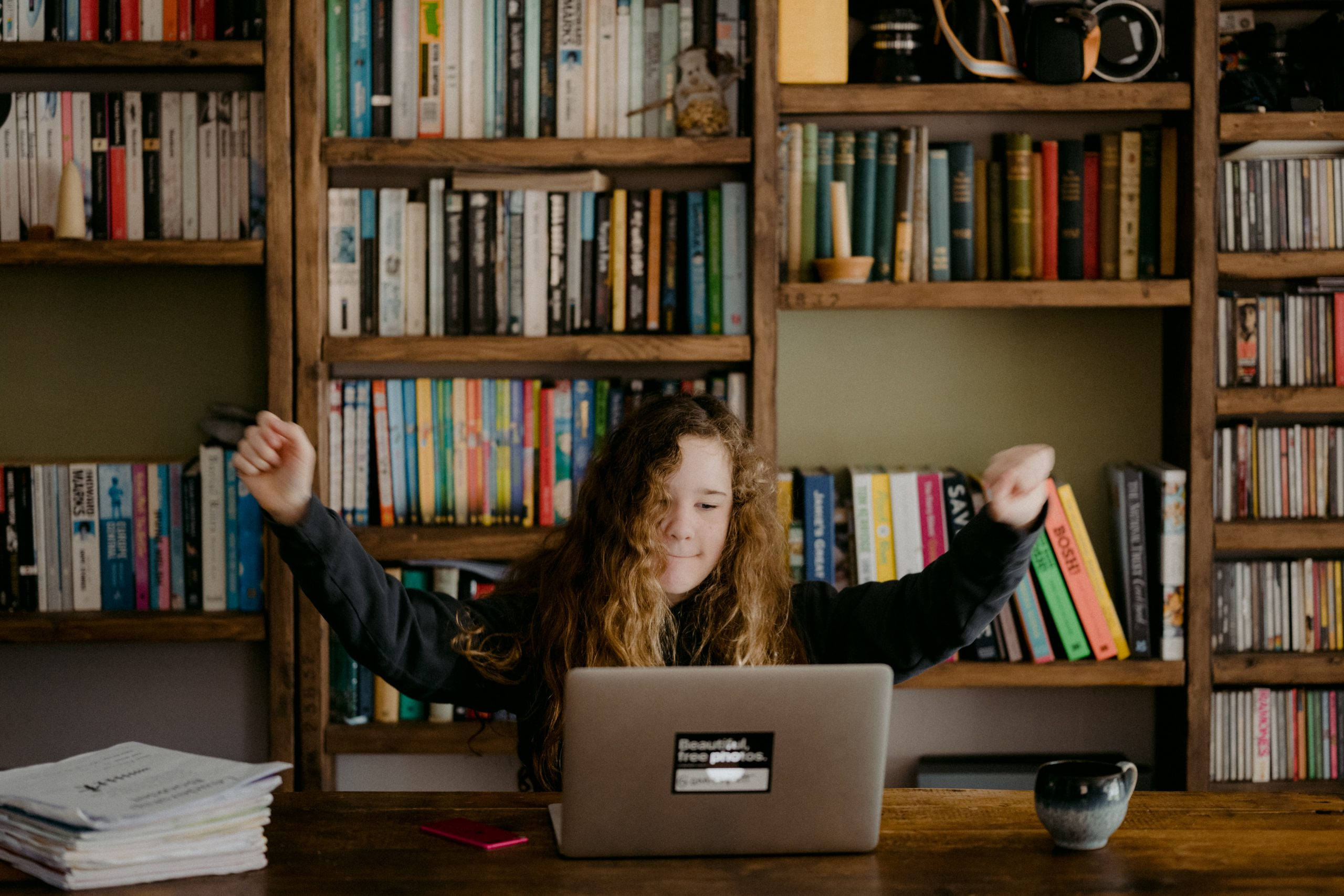 Image shows a child with long brown curly hair, sat at a desk in front of a laptop, celebrating. Bookshelves are in the background.