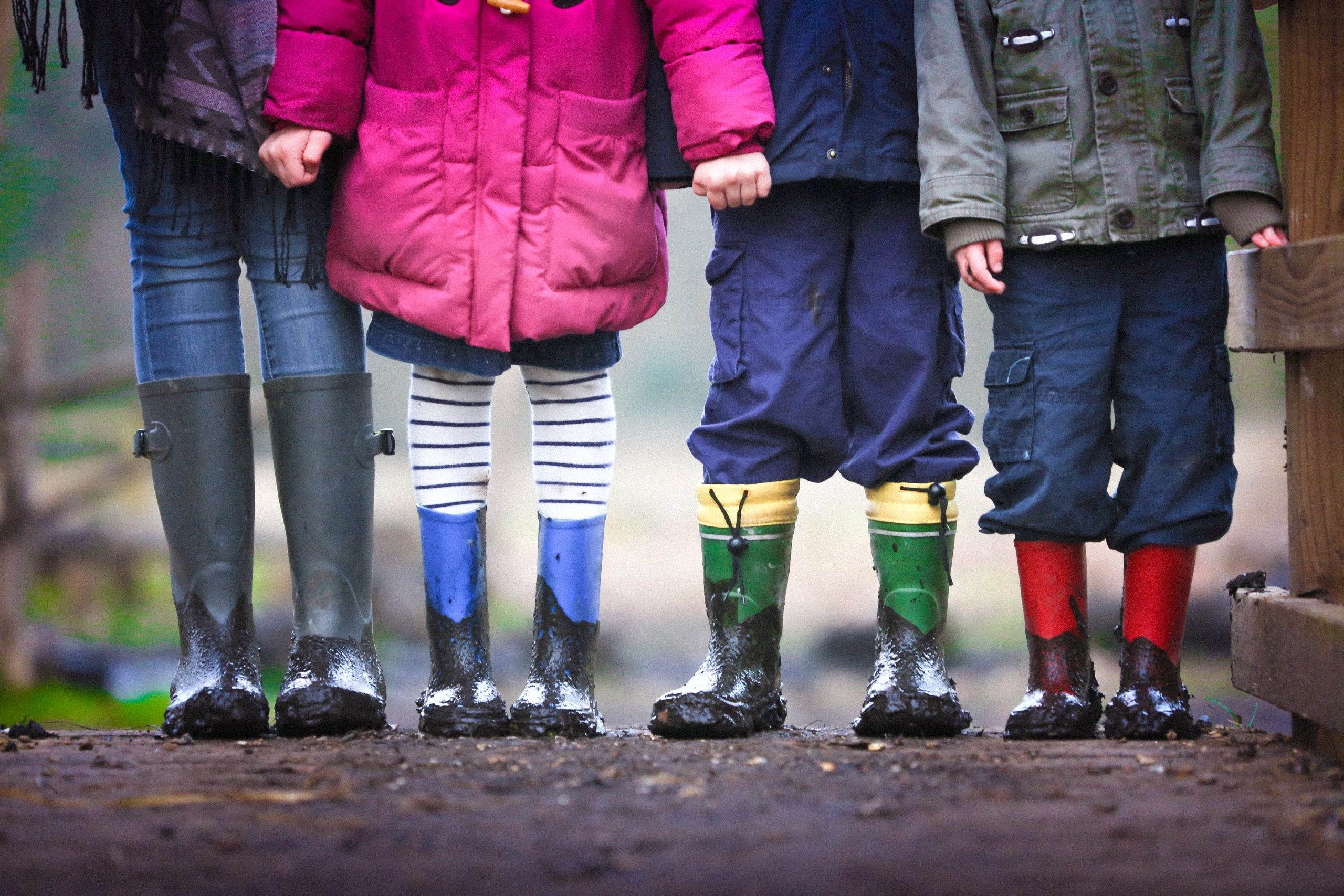 The image shows the legs of four children in a row, all wearing muddy welly boots.