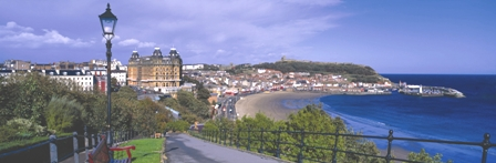 Landscape image shows long, curved stretch of beach, an azure blue sea and Scarborough town.